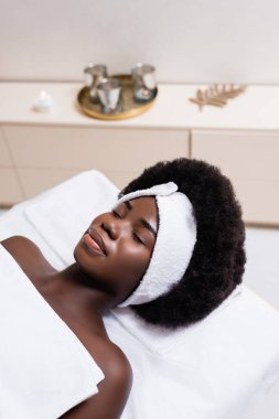 African american woman in white headband covered with bed sheet lying on massage table in spa salon on blurred background