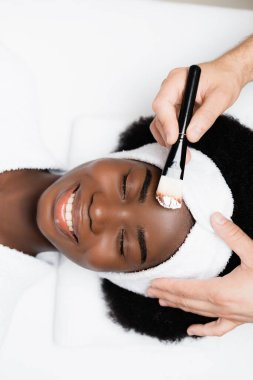 Top view of happy african american with closed eyes lying near man with cosmetic brush in spa salon stock vector
