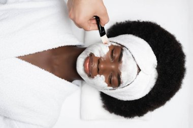 Top view of african american woman with closed eyes, wearing bathrobe, while lying near man applying face mask on cheek in spa salon stock vector