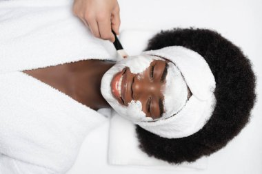 Top view of happy african american woman lying near man applying face mask with cosmetic brush on cheek stock vector