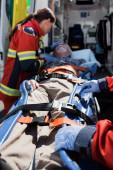 Selektivní zaměření zdravotníků stojících poblíž pacienta na nosítkách a sanitce auto