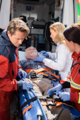 Photo Selective focus of paramedics and doctor standing near senior patient on stretcher and ambulance car