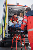 Photo Selective focus of paramedic carrying stretcher with patient near doctor with digital tablet in ambulance car