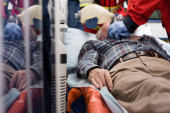 Selective focus of elderly patient lying in ambulance car while paramedics doing cardiopulmonary resuscitation