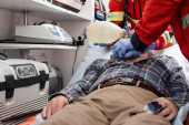Selective focus of paramedics doing cardiopulmonary resuscitation to patient with heart rate monitor in ambulance car
