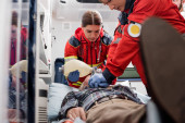 Selective focus of paramedics in uniform doing cardiopulmonary resuscitation to man during first aid
