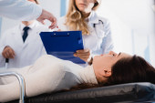 Selective focus of patient with closed eyes lying near doctor pointing at clipboard to colleague in clinic