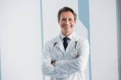 Arzt mit verschränkten Armen blickt in Klinik in die Kamera