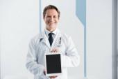 Lékař v bílém plášti při pohledu na fotoaparát a ukazující digitální tablet s prázdnou obrazovkou v nemocnici