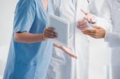Fotografie Ausgeschnittene Ansicht einer Krankenschwester mit digitalem Tablet in der Nähe von Ärzten in der Klinik