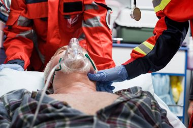 Selective focus of paramedic in latex glove checking pulse of senior patient in oxygen mask near colleague during first aid stock vector