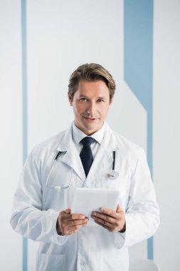 Doctor in white coat holding digital tablet in clinic stock vector