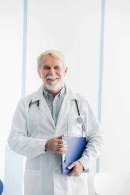 Senior doctor holding clipboard while working in clinic stock vector