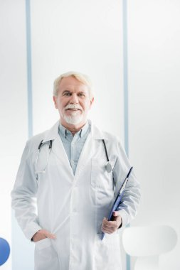 Elderly doctor with clipboard looking at camera in hospital stock vector