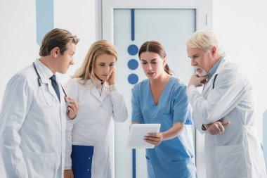 Nurse showing digital tablet to doctors in hospital stock vector