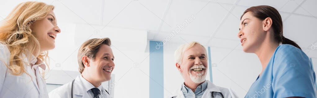 Panoramic shot of doctors looking at nurse while talking in clinic stock vector