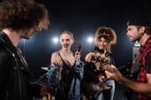 KYIV, UKRAINE - AUGUST 25, 2020: Szkeptikus szőke nő gesztikulál és nézi dobverők közben rock zenekar próba elmosódott előtérben