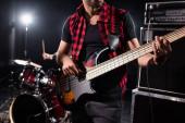 KIEW, UKRAINE - 25. AUGUST 2020: Ausgeschnittene Ansicht eines Bassgitarristen mit verschwommenem Schlagzeuger im Hintergrund, Banner