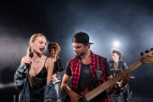 KYIV, UKRAINE - AUGUST 25, 2020: Smiling blonde woman singing near guitarist during rock band rehearsal with backlit on blurred background
