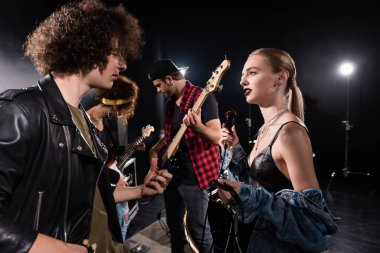 KYIV, UKRAINE - AUGUST 25, 2020: Rock band musician and blonde woman with microphone talking near guitarists with backlit on background
