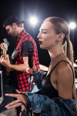 KYIV, UKRAINE - AUGUST 25, 2020: Blonde woman gesturing while holding microphone, standing near guitarist on blurred background stock vector
