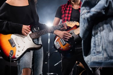 KYIV, UKRAINE - AUGUST 25, 2020: Cropped view of rock band musicians playing electric guitars with blurred jeans jacket on foreground stock vector