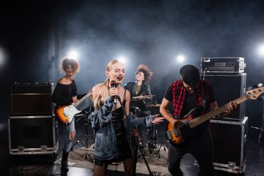 KYIV, UKRAINE - AUGUST 25, 2020: Woman with closed eyes singing while holding microphone rack near rock band musicians on blurred background