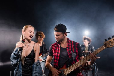 KYIV, UKRAINE - AUGUST 25, 2020: Smiling blonde woman singing near guitarist during rock band rehearsal with backlit on blurred background stock vector