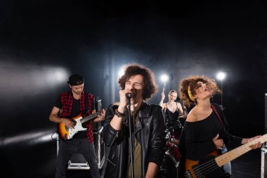 KYIV, UKRAINE - AUGUST 25, 2020: Curly vocalist with closed eyes singing in microphone near guitarists with backlit and female drummer on background stock vector