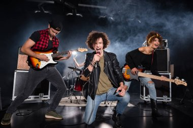 KYIV, UKRAINE - AUGUST 25, 2020: Curly vocalist shouting in microphone while sitting on knee near guitarists during rock band performance with backlit on black stock vector
