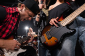 KYIV, UKRAINE - 25.AUGUST, 2020: Kytarista křičí a naklání se k rockovým muzikantům s rozmazaným podsvícením na pozadí
