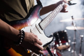 KYIV, UKRAINE - AUGUST 25, 2020: Cropped view of rock band guitarist holding guitar pick near strings on blurred background