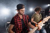 KYIV, UKRAINE - AUGUST 25, 2020: Elektromos gitáron játszó zenészek háttérvilágítással homályos háttérrel