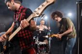KYIV, UKRAINE - 25.AUGUST, 2020: Seriózní hudebník hrající na elektrickou kytaru s podsvícenými a rozmazanými členy rockové kapely na pozadí