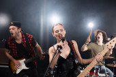KYIV, UKRAINE - AUGUST 25, 2020: Blonde vocalist with electric guitar singing in microphone near guitarist and drummer with backlit on blurred background