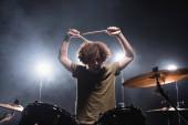 Kudrnatý hudebník křičí, zatímco drží stehna a sedí na buben kit s podsvícením na pozadí