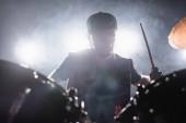 Rock zenekar zenész dobverő játszik dob füst és háttérvilágítás a háttérben