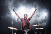 Shouting drummer with hands in air sitting at drum kit with backlit and smoke on black