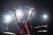 Angry drummer showing rock signs yelling, while sitting at drum kit with backlit on background