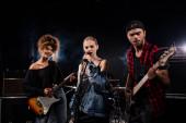 KYIV, UKRAINE - AUGUST 25, 2020: Női énekes rock zenekar mellett álló zenészek elektromos gitárok fekete