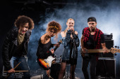 KYIV, UKRAINE - AUGUST 25, 2020: Female vocalist singing, while standing near rock band members with bass guitars and drumsticks, with smoke on black