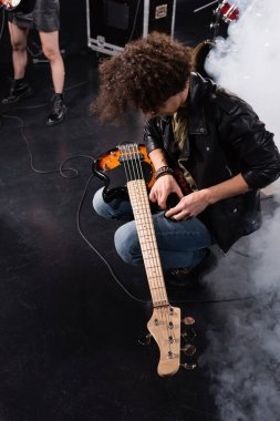 KYIV, UKRAINE - AUGUST 25, 2020: Overhead view of curly musician squatting with electric guitar on knees during rock band rehearsal stock vector