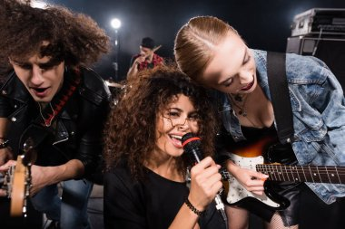 KYIV, UKRAINE - AUGUST 25, 2020: Curly woman with microphone looking at camera near rock band guitarists with backlit and blurred drummer on background stock vector