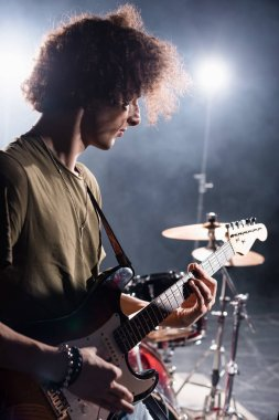 KYIV, UKRAINE - AUGUST 25, 2020: Curly musician playing bass guitar while standing near drum kit with backlit on blurred background stock vector