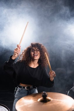 Female drummer with closed eyes shouting, while playing on drum plate with smoke on black background