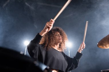 Rock band musician with drumsticks playing on cymbal on blurred foreground