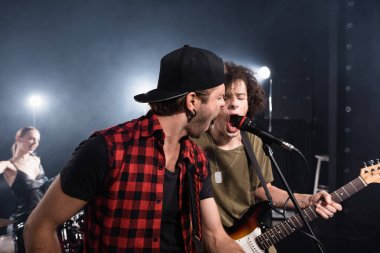 KYIV, UKRAINE - AUGUST 25, 2020: Rock band musicians shouting in microphone with blurred drummer on background