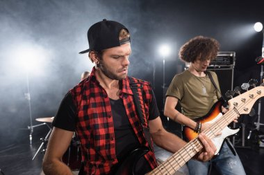 KYIV, UKRAINE - AUGUST 25, 2020: Musicians playing electric guitars with backlit on blurred background stock vector