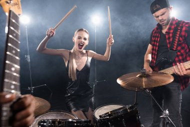 KYIV, UKRAINE - AUGUST 25, 2020: Blonde woman with drumsticks shouting while sitting at drum kit near guitarist with backlit and blurred guitar on foreground stock vector