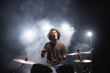 Excited curly drummer with open mouth sitting at drum kit with smoke and backlit on black